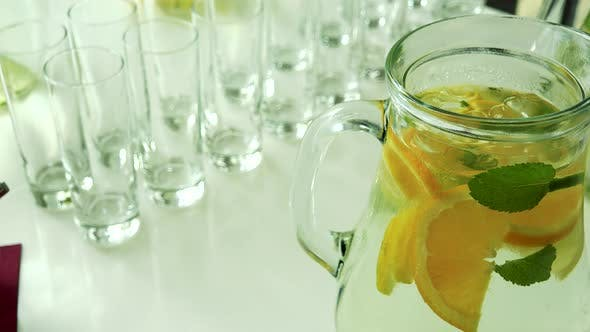 Thumbnail for Jug of Water with Lemon and Several Empty Glasses on the Table in Restaurant