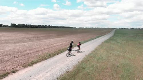 Cyclists riding on gravel bicycles on rural road at countryside