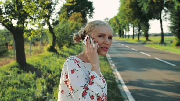 Thumbnail for Woman Speaking on Phone While Hitchhiking.