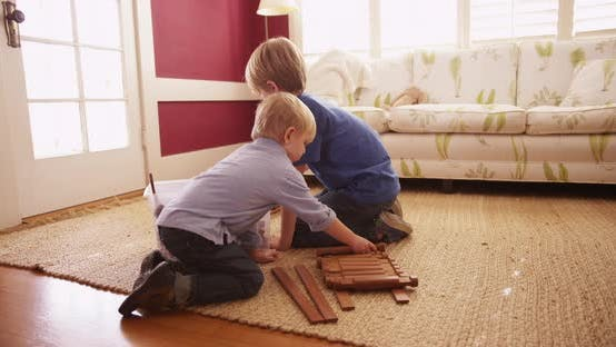 Thumbnail for Two adorable young brothers building a miniature log cabin