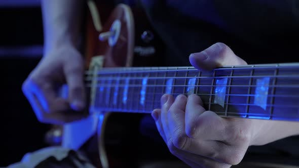 Guitarist playing on electric guitar, recording rock pop song at recording studio.