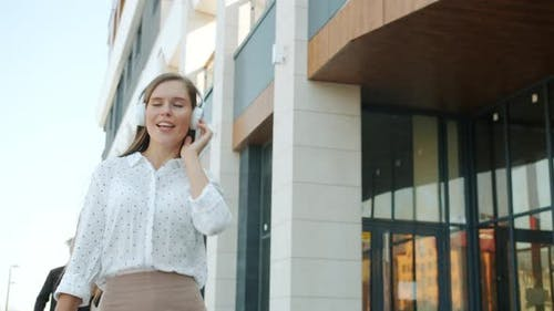 Dolly Shot of Cheerful Businesswoman Wearing Headphones Walking Outdoors Dancing Having Fun in City