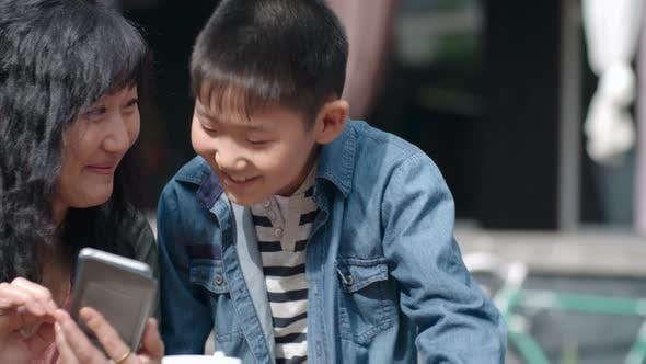 Thumbnail for Asian Woman and Little Boy Smiling and Using Smartphone Outdoors