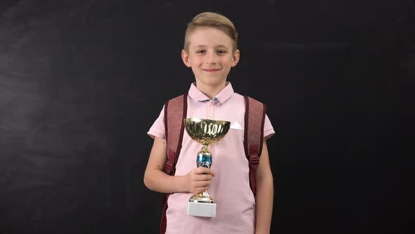Smiling Primary Schoolboy Holding Cup Award, Championship Winner, Success
