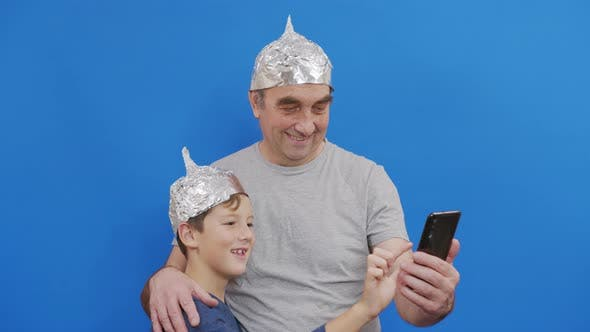Grandfather with His Grandson in Protective Foil Hats From 5g Radiation Standing on a Blue