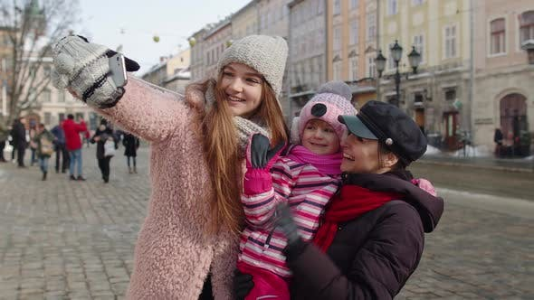 Women Tourists Taking Selfie Photos on Mobile Phone with Adoption Child Girl on Winter City Street