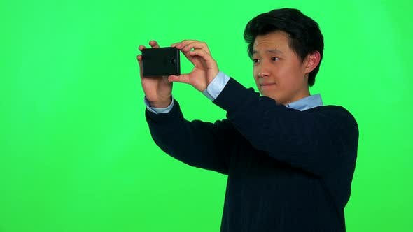Thumbnail for A Young Asian Man Takes a Picture of Something Off the Camera with His Smartphone - Green Screen