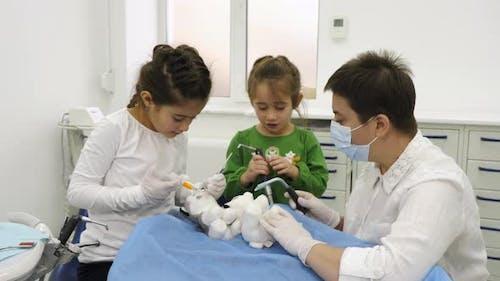 Zahnarzt lehrt Mädchen, wie man Patienten behandelt