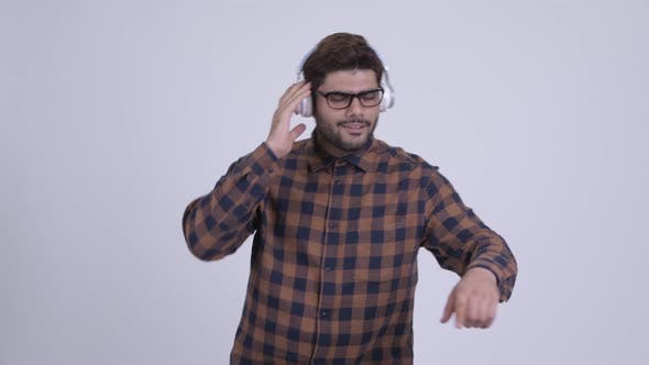 Thumbnail for Happy Young Bearded Indian Hipster Man Listening To Music