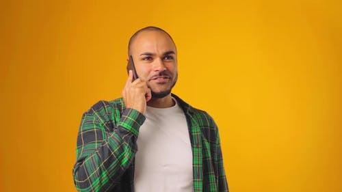 Worried Anxious Man Talking on Mobile Phone Against Yellow Background