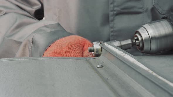 Closeup Worker Locksmith Tightens Nut with Screwdriver Closeup. The Master Tightens a Nut Metal
