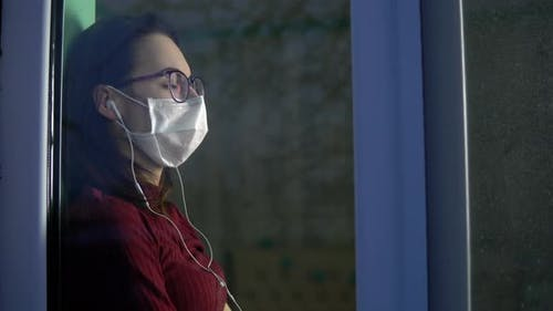 A Young Woman Is Sitting at Home in Quarantine with Headphones in Her Ears. A Girl Sits on a Window