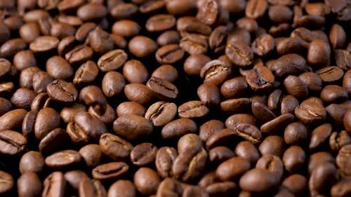 Roasted coffee beans. Slow motion of arabica coffee seeds falling.