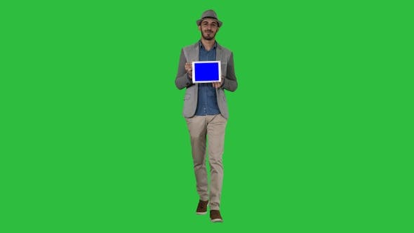 Cover Image for Casual man in a hat walking and showing digital tablet