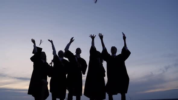 Thumbnail for Silhouette of Graduating Students Throwing Caps In The Air