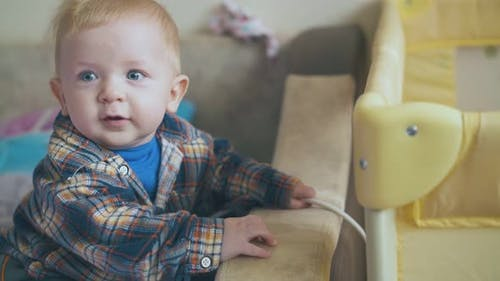 Cute Boy in Shirt Plays with Cable Standing at Playpen