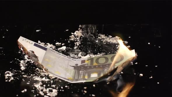 Thumbnail for One hundred euro is flaming and falling on a black table