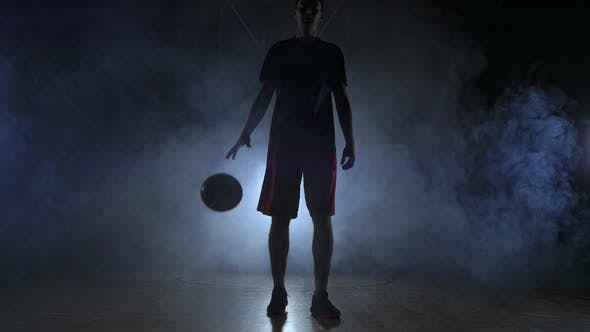 Thumbnail for Basketball Player in Sportswear Red Shorts and a Blue T-shirt Goes on a Dark Basketball Court in the