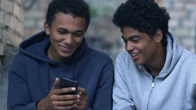 Black male teenager showing friend photos on smartphone