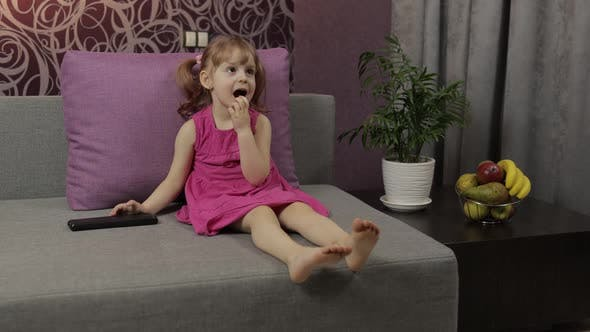 Thumbnail for Little Child Sitting on Couch While Watching TV. Kid Girl Watch Television