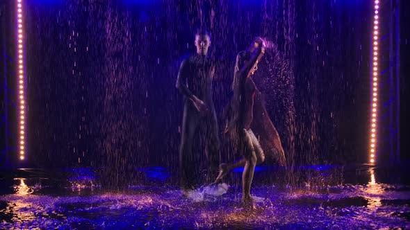 Thumbnail for Silhouettes of Ballroom Dancers in the Rain Perform a Perky Jive Dance. Slow Motion.