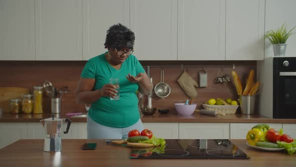 Sick Mature Black Woman Taking Pills in Kitchen