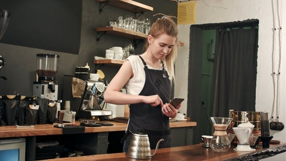 Thumbnail for Cheerful and content female barista using mobile phone