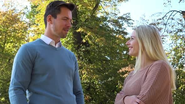 Thumbnail for Ein Mann und eine Frau haben ein Gespräch in einem Park an einem sonnigen Tag - Nahaufnahme von unten