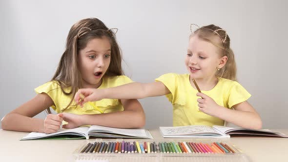 Funny and Funny Children. Children at the Table Dance and Create. Two Children Are Sitting at a