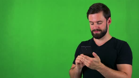 Thumbnail for Young Handsome Bearded Man Works (Typing) on Smartphone - Green Screen - Studio