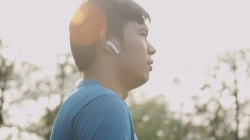 Asian man using wireless earphones on running outdoors at the park. Active lifestyle concept.