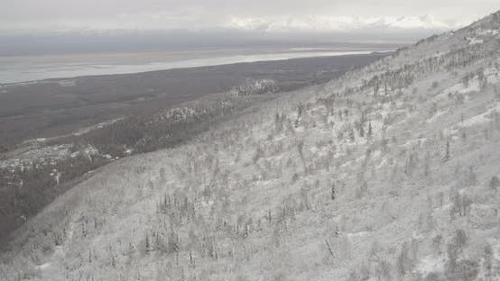 Thumbnail for Aerial helicopter flyover of Alaskan bay at sunrise, mountains, icy water, drone footage