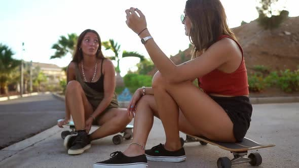 Thumbnail for Two Girls in Skate Park Sit on Boards and Talk Smiling and Laughing at Jokes in the Sunset Light
