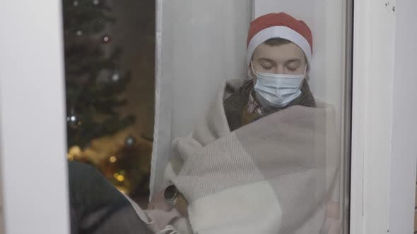 Thumbnail for Exhausted Young Man in Covid19 Face Mask and Christmas Hat Falling Asleep Sitting on Windowsill
