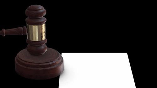 The Judge's Gavel Hits the Wood Next To the Empty Document