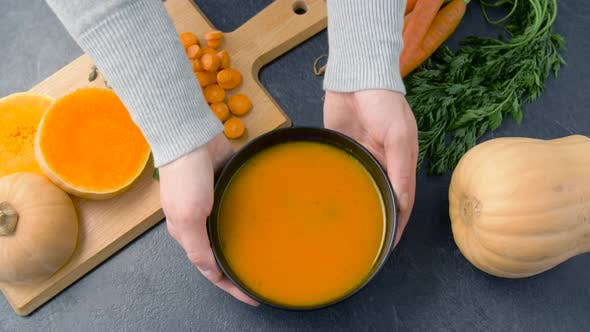 Thumbnail for Hands Putting Bowl of Pumpkin Cream Soup on Table