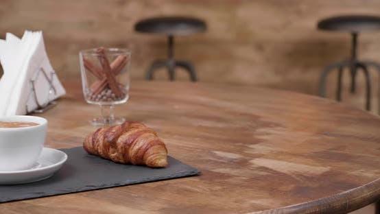 Aufschlussbild einer frischen Tasse schwarzen Coffe mit einem köstlichen Croissant