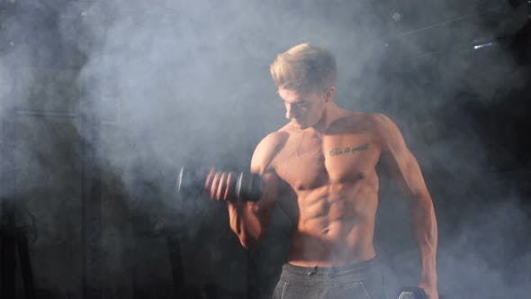 Thumbnail for Shirtless White Man Starting Exercise with Dumbbell Weight in Dark Gym