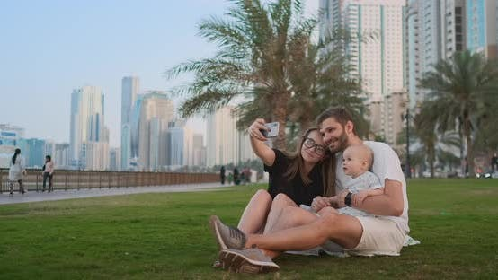 Cover Image for Happy Family with Two Children Sitting Together on Grass in Park and Taking a Selfie. With