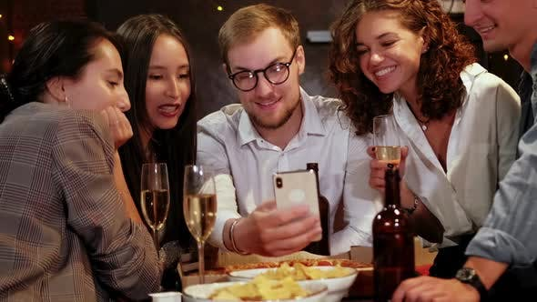 Thumbnail for Company of Focused Hipster Friends Using Smart Phone in the Bar, Pub While Caucasian Man Start