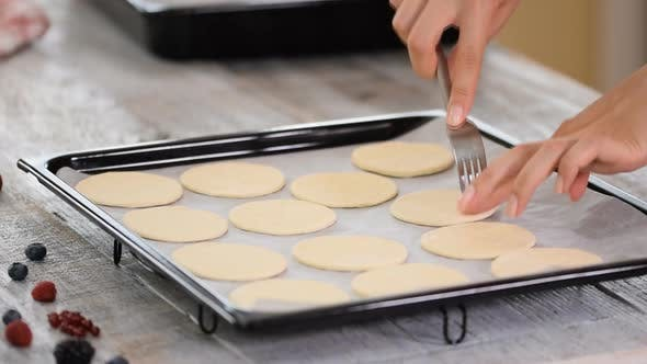 Thumbnail for Woman pierces dough in a baking dish with a fork.