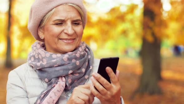 Thumbnail for Happy Senior Woman with Smartphone at Autumn Park 14
