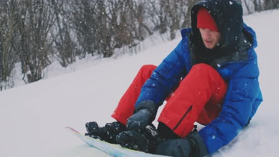 Thumbnail for A Man in Red Pants Sitting on the Snow Fastens Snowboard Boots on the Ski Slope