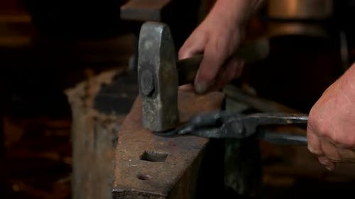 Blacksmith Beating Hot Iron with Hammer on an Anvil