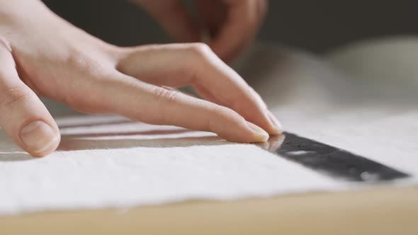 The Seamstress Draws with a Ruler on the Fabric with Chalk