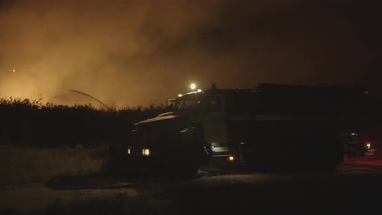Fire Truck with Flashing Lights On. Fire Truck on Background of Burning Grass on Field During Forest