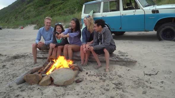 Thumbnail for Group of friends at beach hanging out by campfire