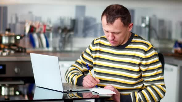 Young Man Working at Home Using Laptop, Making Notes in Notebook