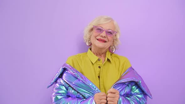 Close Up of a Stylish Older Woman with Blonde Hair and Glasses Posing for the Camera in the Studio