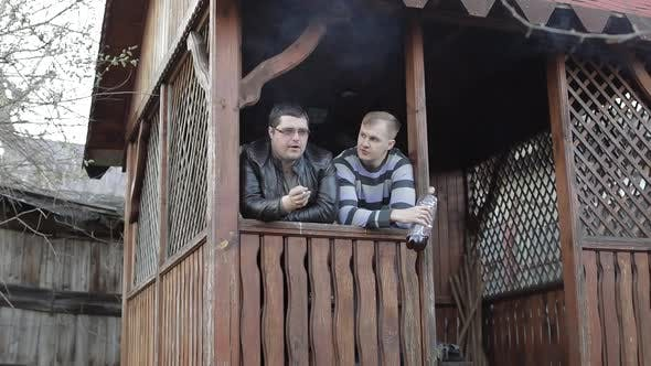 Two Men on Terrace Drink Beer From Plastic Bottle and Smoking